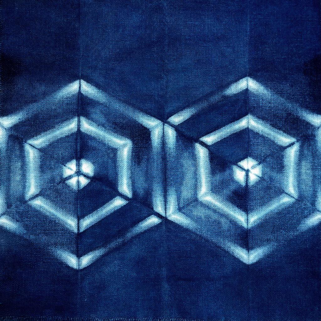 Itajime-shibori teñido con índigo. Plegado triángulo equilátero + reservas pares madera y elásticos
