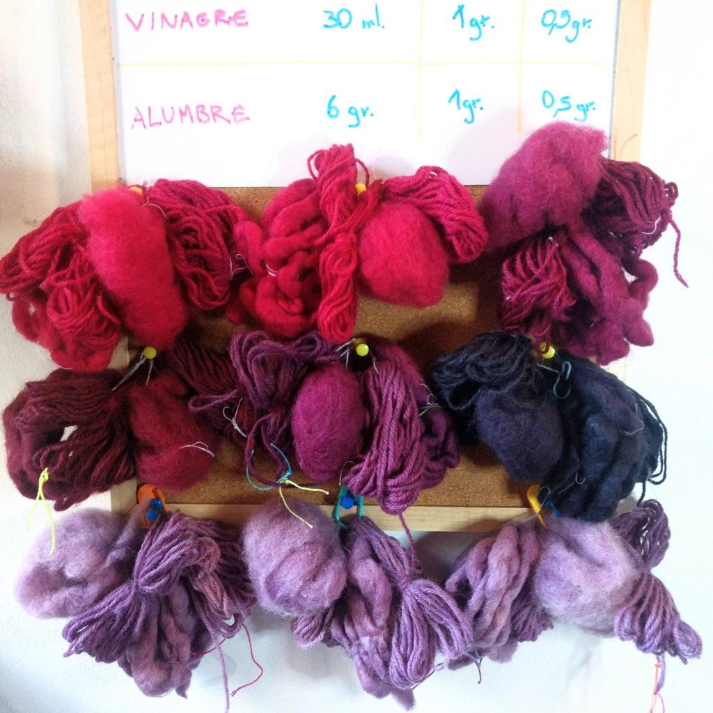 Muestras de lana, vellón y alpaca teñidas con cochinilla y distintos mordientes. Arriba cremor tártaro y alumbre. Al medio vinagre. Abajo alumbre